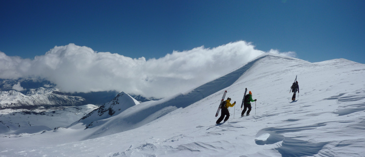 High up on Nevados de Chillan, carrying the skis at the top of a short steep section of sastrugi.